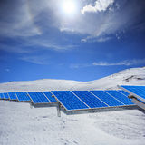 Modern sol- station med blåttpaneler som står i vinterfält w Royaltyfri Foto