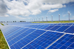 Modern solar station with blue panels and windfarm with wind tur Stock Photos
