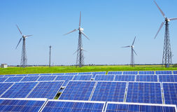Modern solar station with blue panels and windfarm with wind tur Stock Image