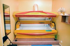 Modern solarium interior. Tanning machine, solarium, open and waiting for clients. Small room, mirror, shelf, a chair Stock Image
