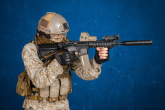 Modern soldier with rifle. On blue background Royalty Free Stock Photography