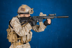 Modern soldier with rifle. On blue background Stock Photos