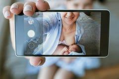 Modern som ammar det nyfödda mobila fotoet, behandla som ett barn Arkivbilder