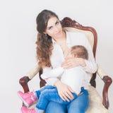 Modern som ammar ett gulligt, behandla som ett barn nyfödd flicka Arkivbilder