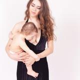 Modern som ammar ett gulligt, behandla som ett barn nyfödd flicka Royaltyfria Foton