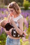 Modern som ammar henne, behandla som ett barn i ett fält av purpurfärgade blommor Royaltyfri Bild
