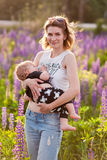 Modern som ammar henne, behandla som ett barn i ett fält av purpurfärgade blommor Arkivbild