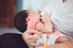Modern som ammar hennes nyfött, behandla som ett barn flickan Royaltyfri Foto