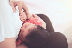 Modern som ammar hennes nyfött, behandla som ett barn flickan Arkivfoto