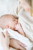 Modern som ammar newbormen, behandla som ett barn - inomhus Royaltyfria Foton