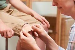 Modern som applicerar bindemedel, förbinder till sonens knä arkivfoto