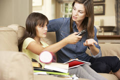 Modern som blir frustrerad som dotter, håller ögonen på TVstund att göra läxasammanträde på Sofa At Home Arkivfoto