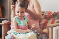 Modern som borstar henne, behandla som ett barn dotterhår hemma Royaltyfri Foto