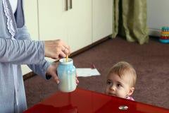 Modern som förbereder sig, mjölkar för ditt barn behandla som ett barn på bakgrund horisontal Fotografering för Bildbyråer