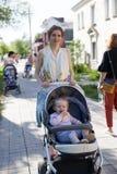 Modern som går i gatan med henne, behandla som ett barn i sittvagn arkivfoto