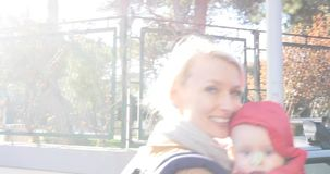 Modern som går med henne, behandla som ett barn i staden som ler lager videofilmer
