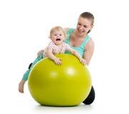 Modern som gör gymnastik, behandla som ett barn på konditionboll Royaltyfri Bild