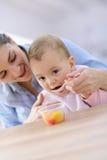 Modern som hjälper henne, behandla som ett barn att äta Royaltyfri Fotografi