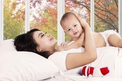 Modern som kramar henne, behandla som ett barn på säng Royaltyfria Foton