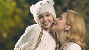 Modern som kysser dottern på kind, den extremt lyckliga flickan som ler på kameran parkerar in stock video