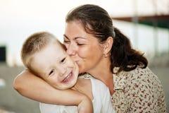 Modern som kysser henne, behandla som ett barn Arkivfoto