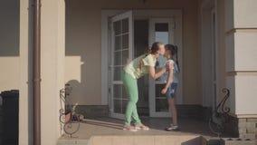 Modern som kysser hennes dotteranseende på farstubron av ett stort hus Barnet som kramar kvinnan Mum och barn arkivfilmer