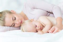 Modern som ligger med hennes litet, behandla som ett barn Arkivfoton