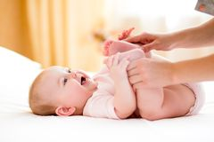 Modern som masserar eller gör gymnastik, behandla som ett barn flickan Fotografering för Bildbyråer