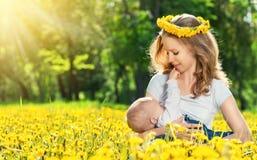 Modern som matar henne, behandla som ett barn i naturgräsplanäng med gult flöde Royaltyfri Foto