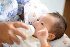 Modern som matar henne, behandla som ett barn spädbarnet från flaskan, behandla som ett barn att dricka mjölkar f Arkivbild