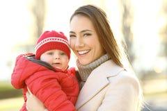 Modern som poserar med henne, behandla som ett barn sonen i vinter Royaltyfri Fotografi