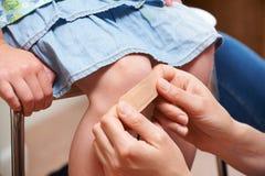 Modern som sätter bindemedel, förbinder på dotterns knä royaltyfri bild