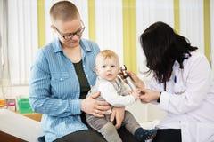 Modern som ser, behandla som ett barn att undersökas av den kvinnliga doktorn Fotografering för Bildbyråer