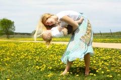Modern som spelar med, behandla som ett barn i maskrosfält Arkivfoton
