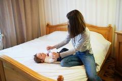 modern som spelar med henne, behandla som ett barn i sovrummet lycklig familj royaltyfria bilder