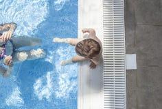 Modern som spelar med henne, behandla som ett barn på simbassängen inomhus arkivbild
