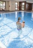 Modern som spelar med henne, behandla som ett barn på simbassängen inomhus arkivfoto