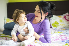 Modern som talar med, behandla som ett barn sonen i säng royaltyfri bild