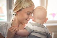 Modern som tycker om med hennes, behandla som ett barn pojken hemma royaltyfri bild