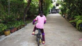 Modern som undervisar hennes dotter att rida på två hjul, cyklar hemma arkivfilmer