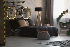 Modern sovruminre med dekorativa kuddar på svart säng, a royaltyfria bilder