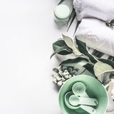 Modern spa background with white towels, tools and green herbs, top view, place for your design. Wellness treatment , skin and body care concept royalty free stock photography