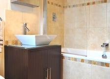 Modern spa bathroom. Basin, bath and tap in tiled wall in a modern spa bathroom Royalty Free Stock Image