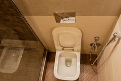 Toilet with integrated drain tank and shower. View from above. stock image
