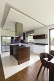 Modern and spacious kitchen. With white walls and steely fridge Stock Photos