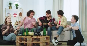 In a modern spacious living room group of friends enjoy the time together on the sofa playing on a guitar singing and. Happy spending a great time. shot on red stock video footage