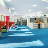 Modern university library with reception. Modern and spacious university library with reception and blue carpet royalty free stock photo