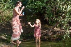 Modern spelar i dottern som startar upp såpbubblor Arkivbild
