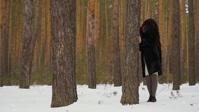Modern spelar kurragömma med dottern i vinterskog arkivfilmer