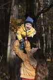 Modern spelar med det skratta barnet som upp kastar honom upp mot Royaltyfri Foto